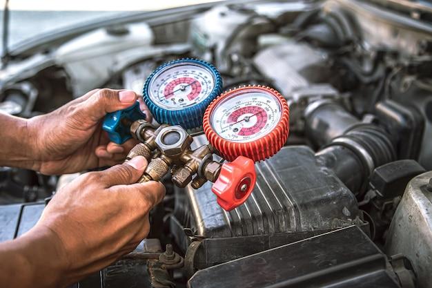 Fermer la main à l'aide de la jauge de collecteur pour remplir les vieux climatiseurs de voiture.