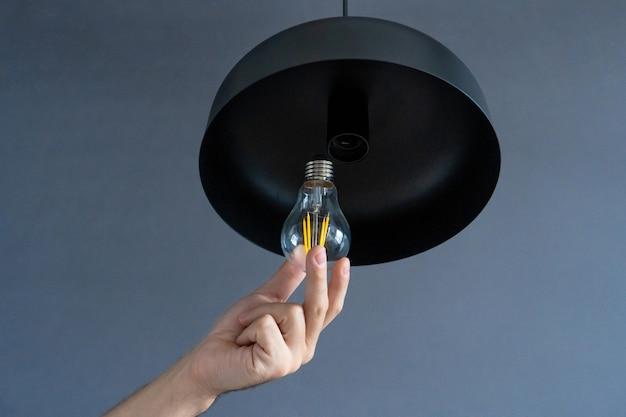 Fermer. une main change une ampoule dans une lampe loft élégante. lampe à filament en spirale. décoration intérieure moderne.