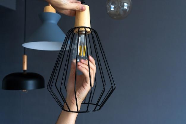 Fermer. une main change une ampoule dans une lampe loft élégante. lampe à incandescence en spirale. décoration intérieure moderne.