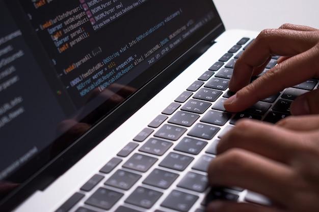 Fermer. la main du développeur crée du code sur un moniteur d'ordinateur sur un bureau blanc.