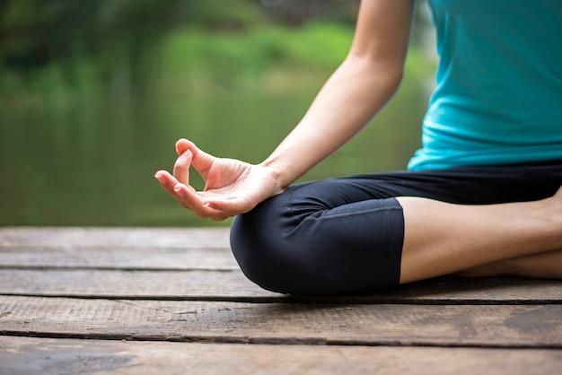 Fermer la main. femme faire yoda en plein air. femme faisant du yoga au fond de la nature