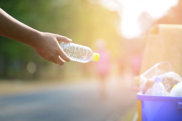 Fermer la main de personnes tenant jeter une bouteille en plastique vide dans la poubelle avec la lumière du soleil.