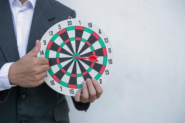 Fermer une main vise la flèche de fléchette verte vers le centre du jeu de fléchettes.