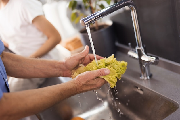 Fermer. les mains des hommes lavent les feuilles de salade sous un jet d'eau.