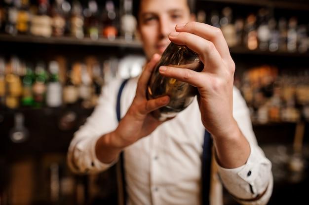 Fermer les mains de jeunes barmans avec shaker