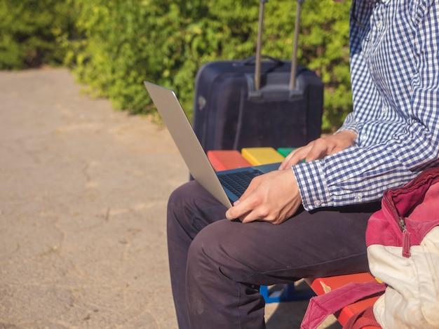 Fermer les mains de la personne assise sur un banc dans la rue travaillant sur ordinateur portable