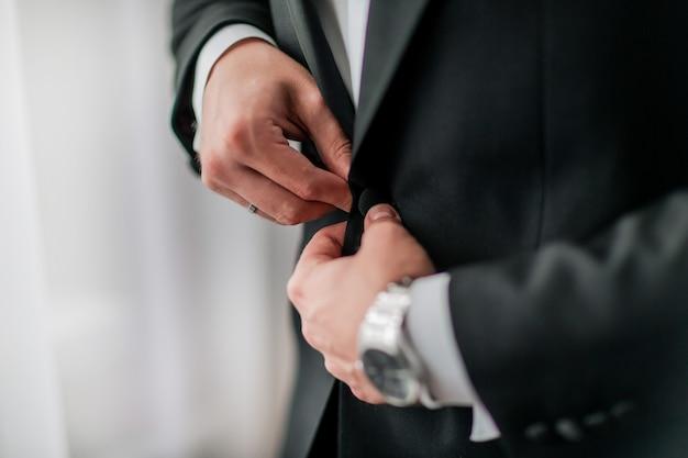 Fermer. marié boutonnant sa veste. vacances et événements