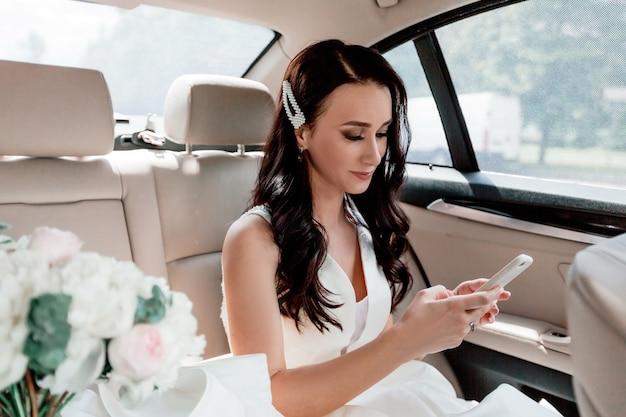Fermer. mariée heureuse avec smartphone assis dans la voiture. vacances et événements