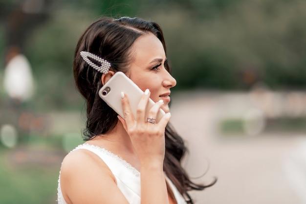 Fermer. mariée parlant sur son smartphone. vacances et événements