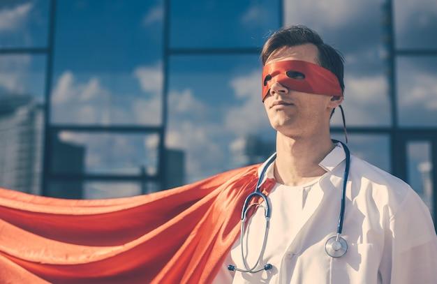 Fermer. médecin héros dans une cape superman debout dans une rue de la ville.