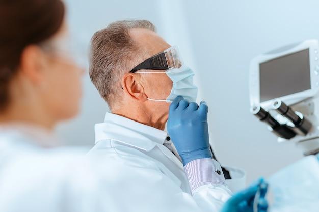 Fermer. médecin mettant un masque de protection en laboratoire.