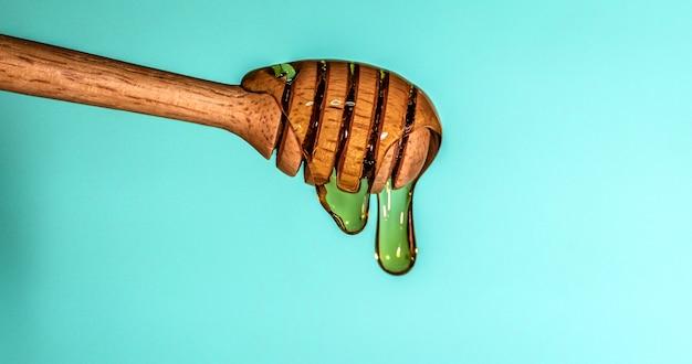 Fermer le miel sucré doré qui coule sur la louche au miel