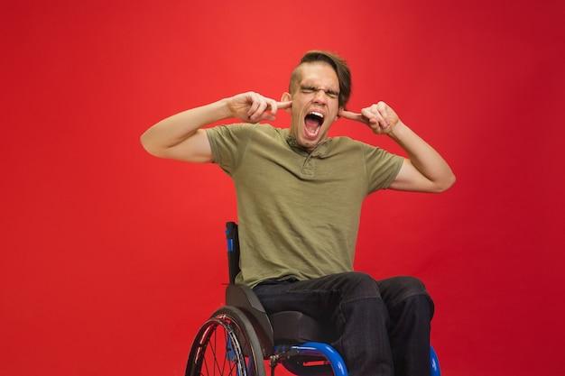Fermer les oreilles. portrait d'un jeune homme handicapé caucasien sur rouge