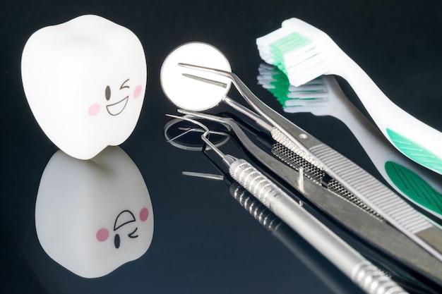 Fermer; outils dentaires et sourire dents modèle sur fond noir.