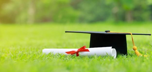 Fermer le papier du certificat et le capuchon de l'éducation sur l'herbe verte au printemps dans le parc extérieur
