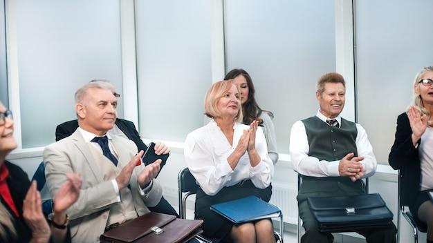 Fermer. les participants au séminaire applaudissent dans la salle de conférence. affaires et éducation