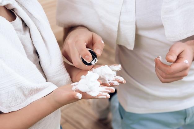 Fermer. le père insère la mousse à raser dans les mains du fils.