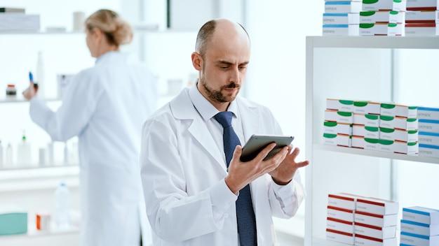 Fermer. pharmacien avec une tablette numérique debout près d'une vitrine avec des médicaments.