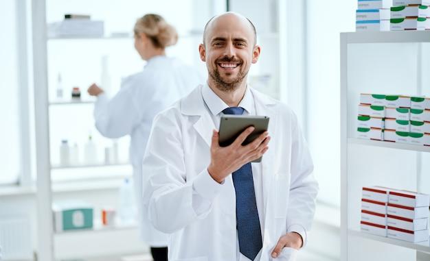 Fermer. pharmacien avec une tablette numérique qui vous regarde.