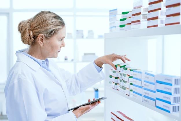 Fermer. pharmacienne sérieuse à l'aide d'une tablette numérique sur le lieu de travail.