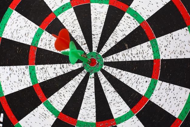 Fermer. plusieurs flèches fléchettes frappant le centre de la cible de fléchettes.le concept de but.
