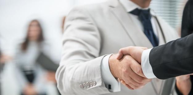 Fermer. poignée de main d'affaires sur fond de bureau. notion de partenariat