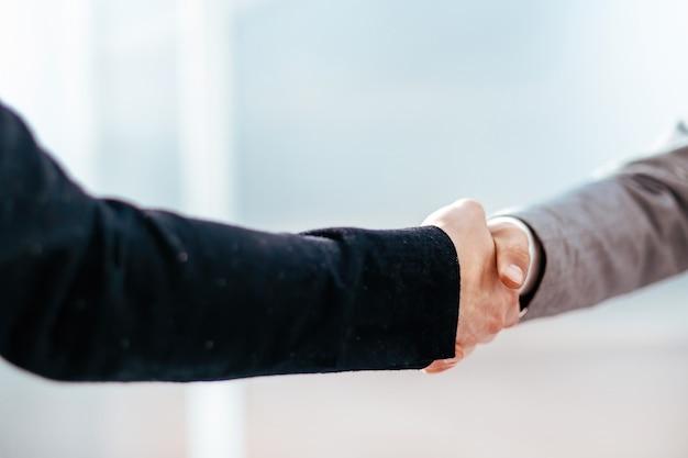 Fermer. poignée de main de gens d'affaires sur le fond d'un bureau lumineux. notion de partenariat