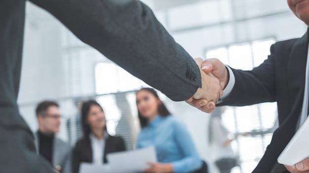 Fermer. poignée de main des partenaires commerciaux en arrière-plan du bureau. concept de coopération