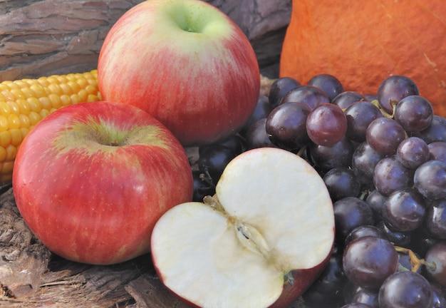 Fermer les pommes rouges coupées au raisin noir amont et autres pommes sur fond en bois