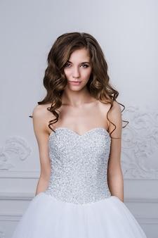 Fermer le portrait de la belle femme mariée souriante aux longs cheveux bouclés posant en robe de mariée à l'intérieur et souriant. portrait intérieur de beauté.