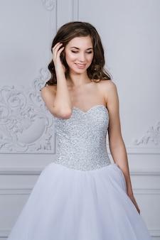 Fermer le portrait de la belle femme mariée souriante aux longs cheveux bouclés posant en robe de mariée à l'intérieur et souriant.