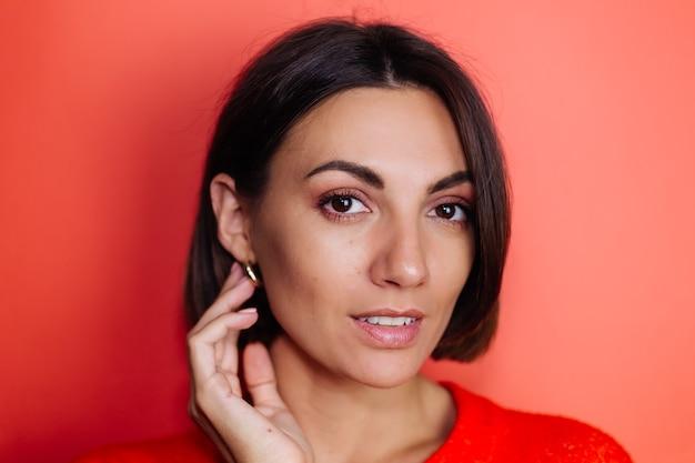 Fermer le portrait de femme sur le mur rouge regarde vers l'avant avec le sourire