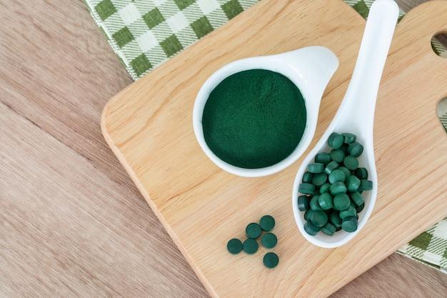 Fermer une poudre de spiruline dans un bol et des pilules de spiruline, un régime alimentaire sain et un concept de nutrition détox