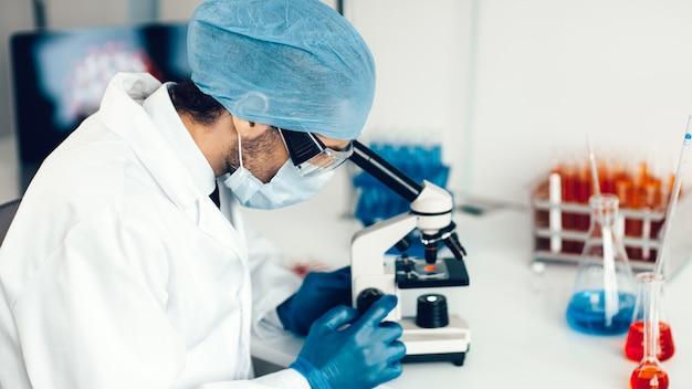 Fermer. scientifique regardant une goutte de sang au microscope.