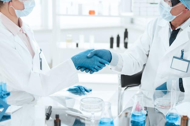 Fermer. scientifiques en microbiologie se serrant la main. science et santé.