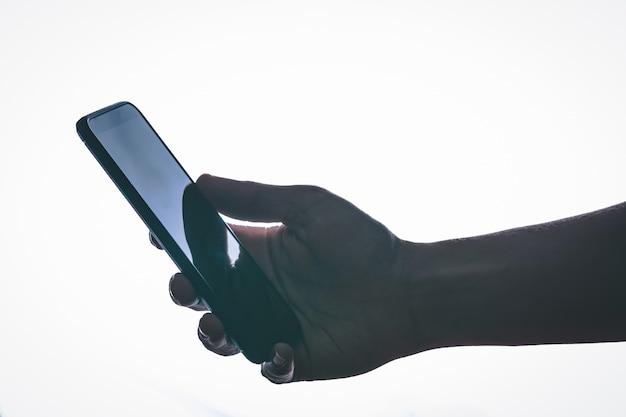 Fermer. smartphone à la main avec rétro-éclairage et style moderne