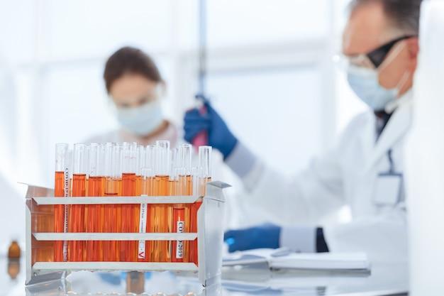 Fermer. stand avec des tubes à essai sur la table dans le laboratoire. photo avec une copie de l'espace.