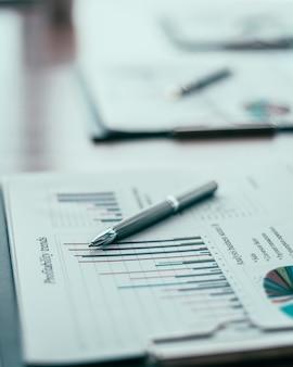 Fermer. tableau financier et stylo sur le bureau. fond d'affaires.