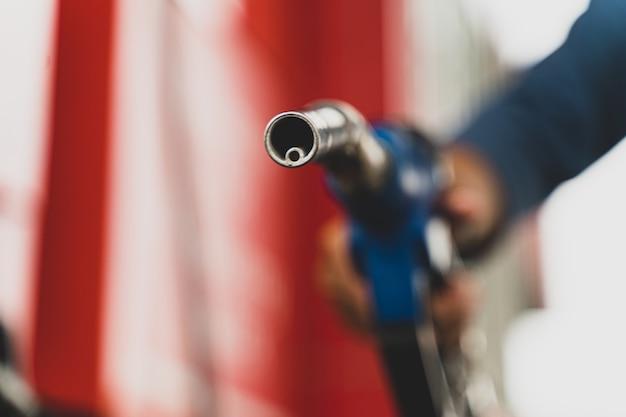 Fermer la tenue à la main du distributeur de carburant de la pompe à essence concept de transport du carburant de l'huile d'essence