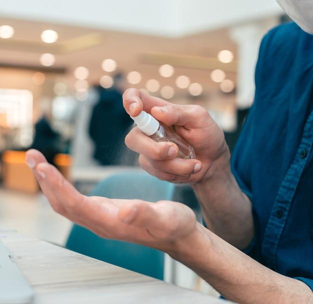 Fermer. vaporiser d'antiseptique dans les mains d'un jeune homme