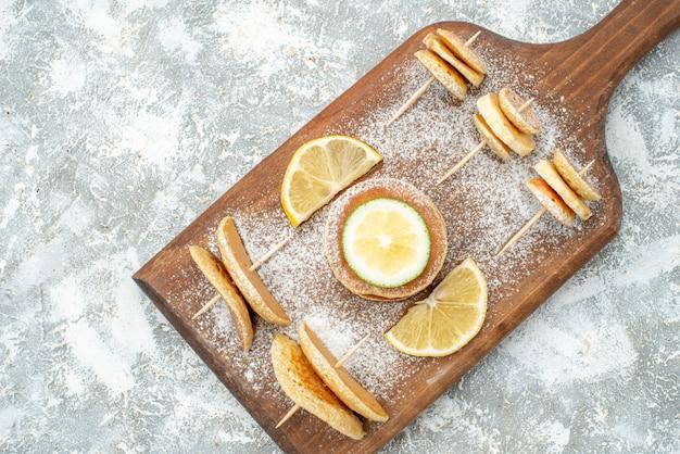 Fermer la vue des crêpes classiques aux citrons sur une planche à découper en bois sur bleu