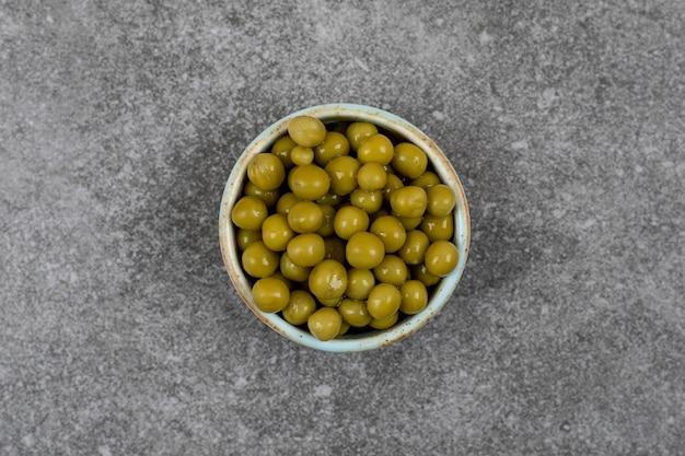 Fermer. vue de dessus des pois en conserve verts dans un bol sur une surface grise