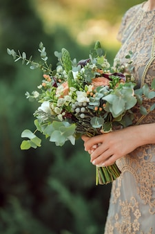 Fermer la vue du beau bouquet de mariage coloré dans une main d'une mariée contre bokeh vert de fond de nature