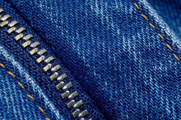 Fermeture éclair en métal sur un jean bleu. macro