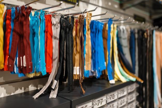 Fermetures à glissière colorées sur étagère dans un magasin de textile, personne. vitrine avec accessoires pour la couture, choix de vêtements en magasin