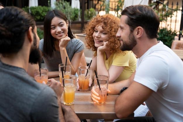 Fermez les amis avec des boissons à table