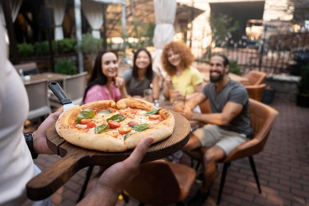 Fermez les amis avec de délicieuses pizzas