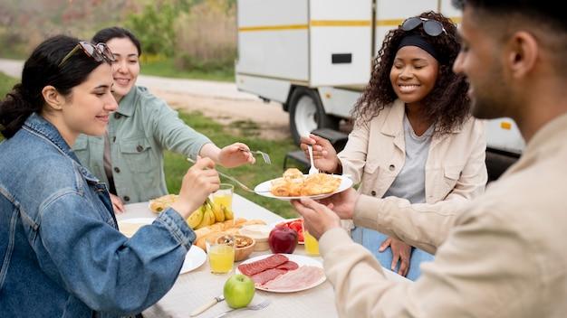Fermez les amis mangeant ensemble dehors