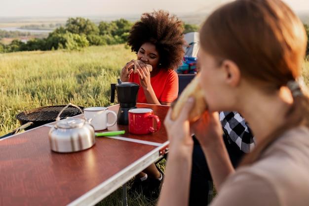 Fermez les amis mangeant ensemble
