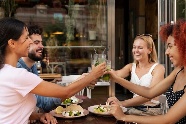 Fermez les amis souriants avec des boissons